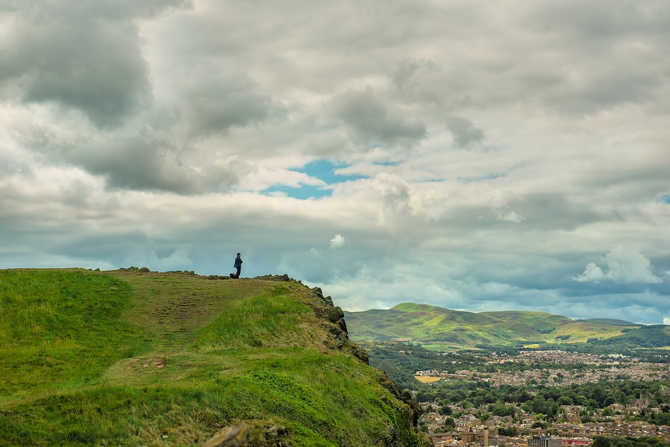 A man looking over the view from Arthur's Seat in Edinburgh on a cloudy day