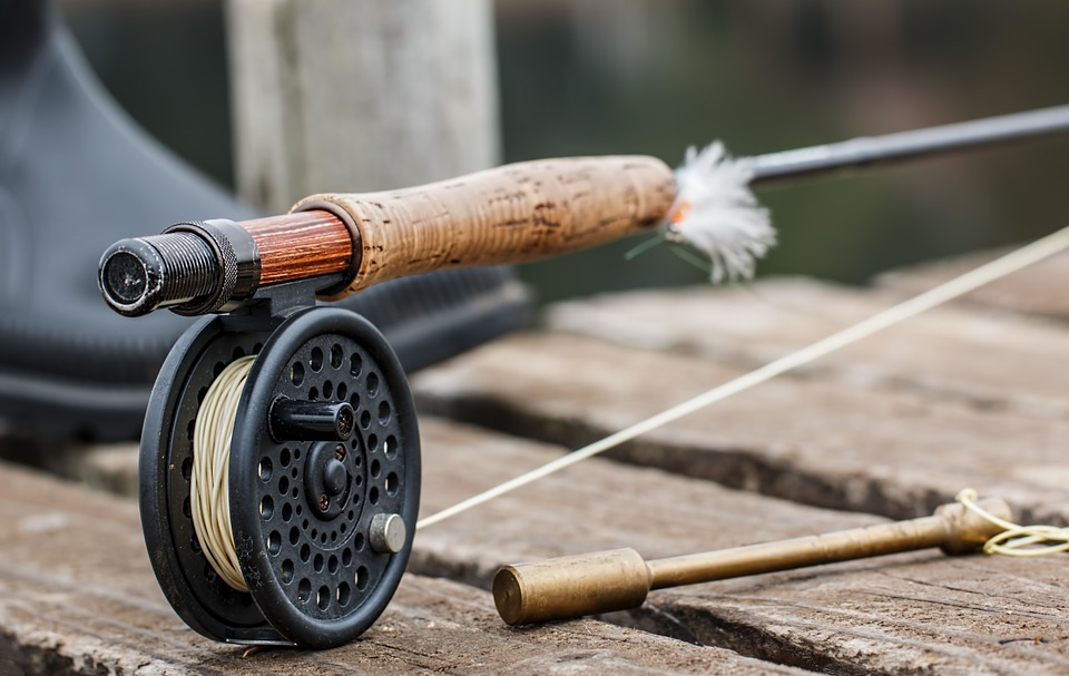 An old, wooden fly-fishing rod, reel and hook