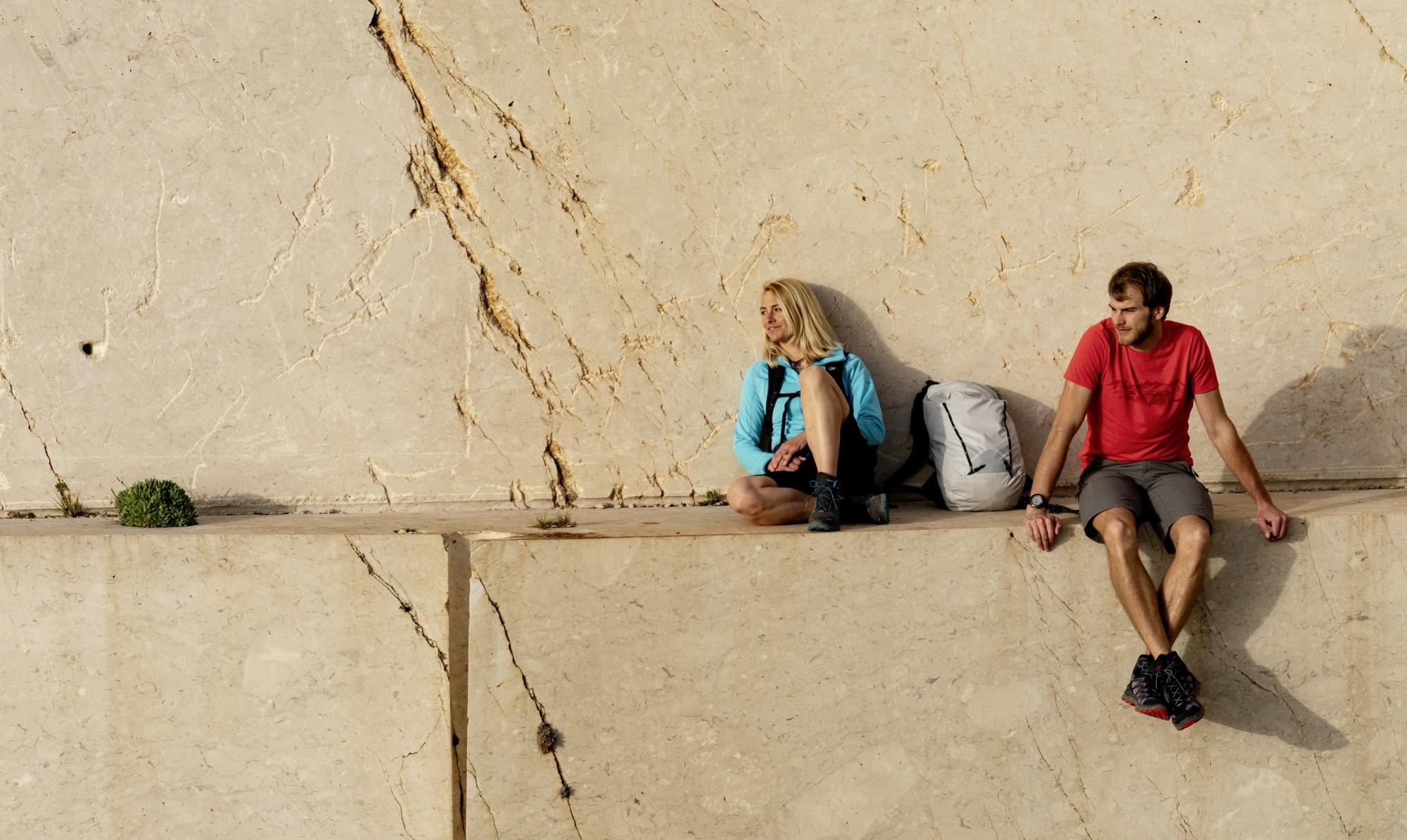 Two active people sitting on a marble wall in LOWA footwear