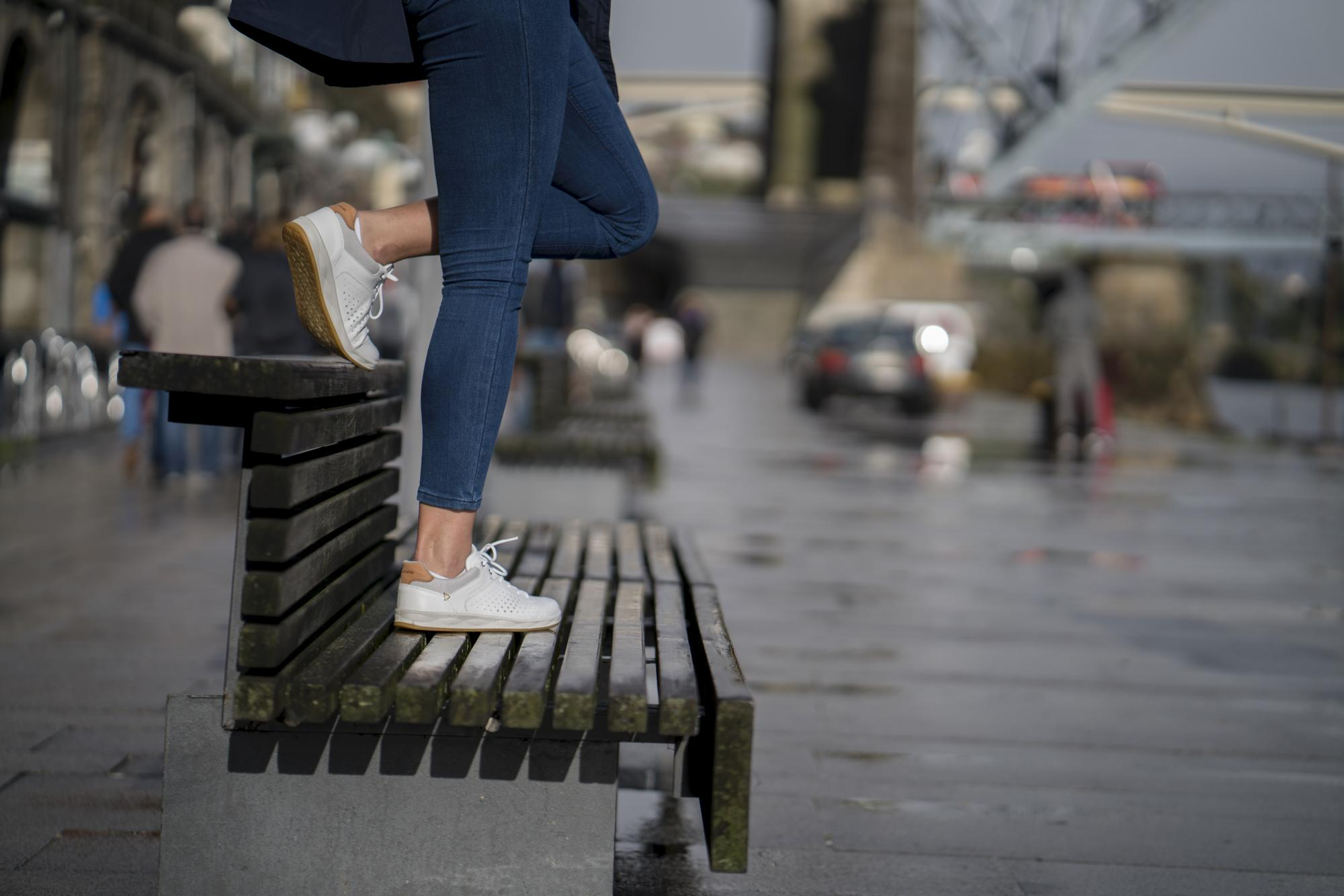 A woman wearing LOWA lo-cut footwear on a city bench