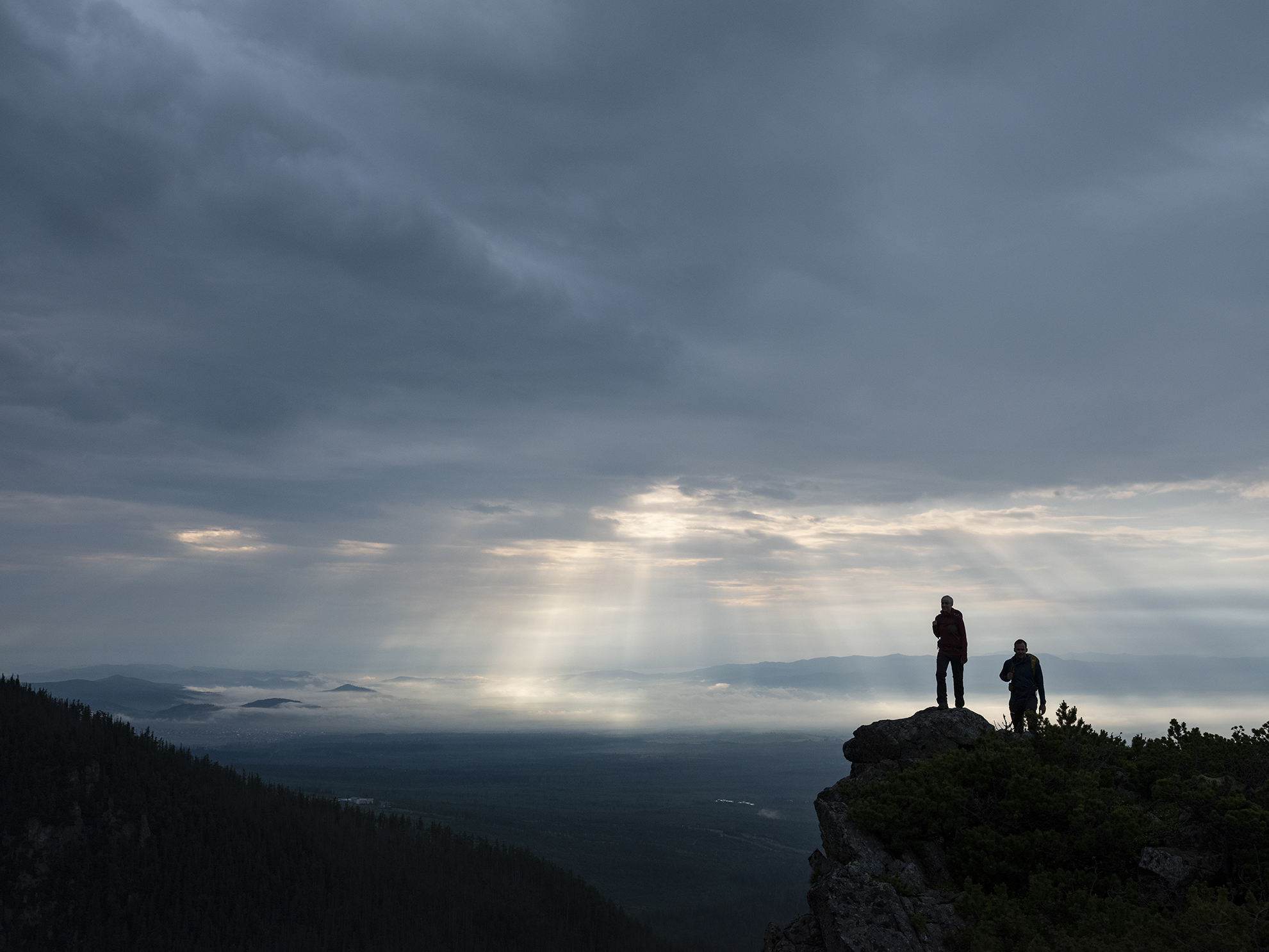 Two hikers on a mountain summit on a cloudy day