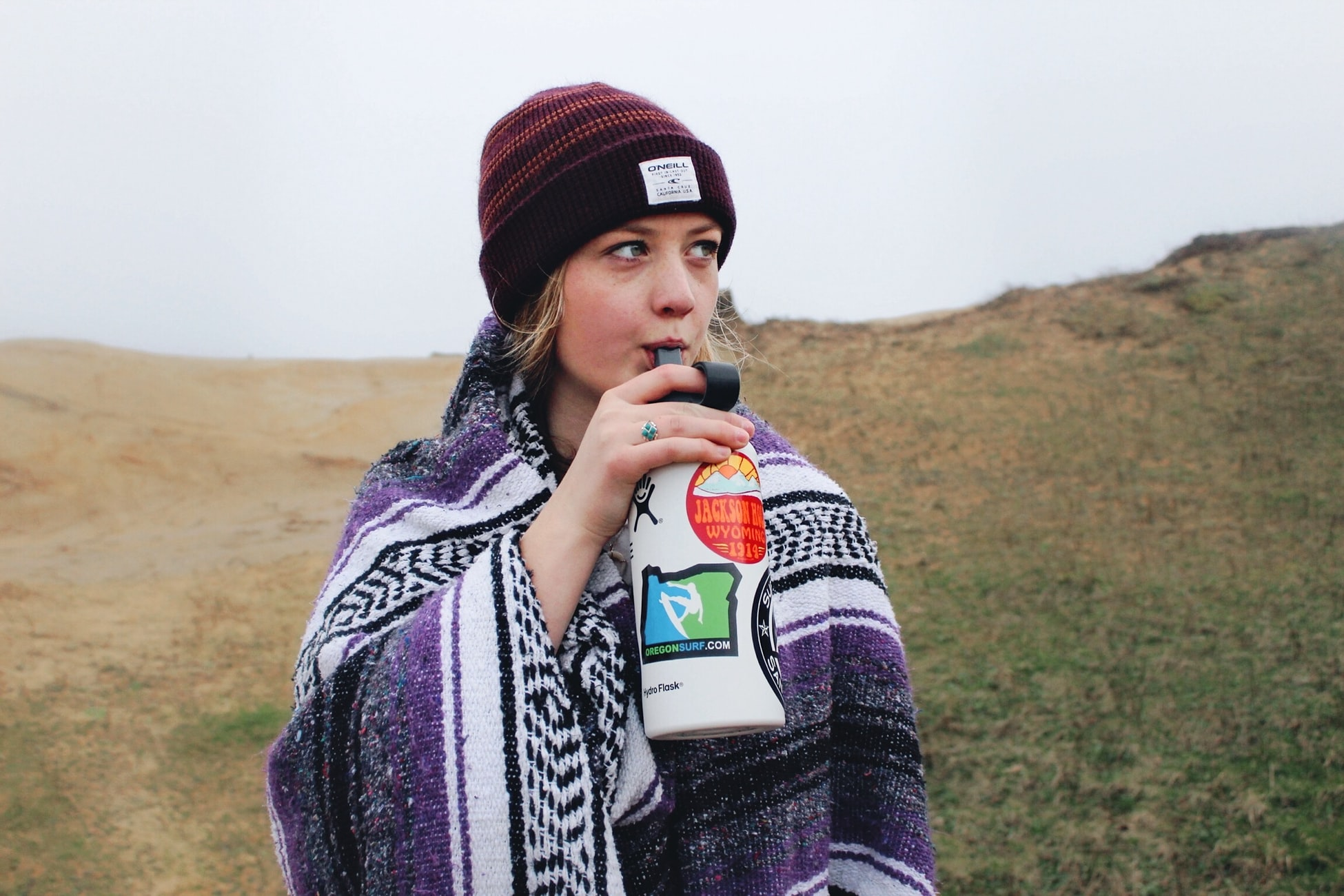 woman drinking from a water bottle on a hike