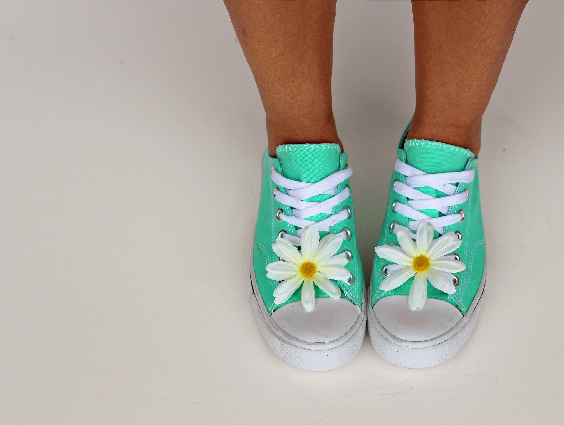 Woman wearing pair of mint coloured converse style trainers.